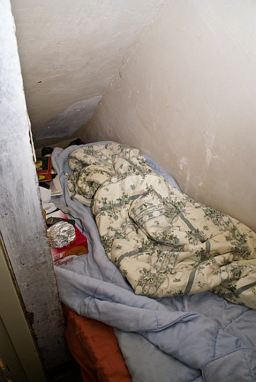 Sleeping space under the stairs in a house packed full of Polish workers.